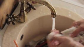 特写镜头供以人员手的洗涤盘、喷水的冲洗从泡沫的板材和洗涤剂 股票录像