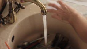 特写镜头供以人员手的洗涤盘、喷水的冲洗从泡沫的板材和洗涤剂 股票视频