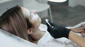 特写镜头侧视图妇女的有注射器的面孔和美容师的手做面部秀丽射入 影视素材