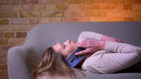特写镜头侧视图画象年轻有吸引力白种人深色女性有电话说谎松弛在长沙发 股票录像