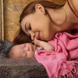 特写镜头俏丽的妇女亲吻她的胳膊的一新生儿 免版税图库摄影