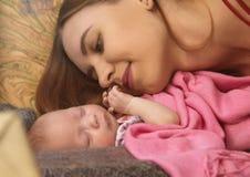 特写镜头俏丽的妇女亲吻她的胳膊的一新生儿 库存图片