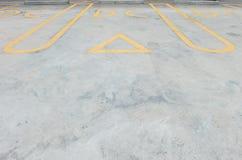 特写镜头停放的槽孔线的表面老和淡黄的被绘的标志在水泥街道地板上在有DC词标志te的停车场 免版税库存照片