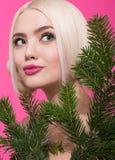 特写镜头偷看从后面杉木的年轻美丽的妇女秀丽画象分支 免版税库存图片