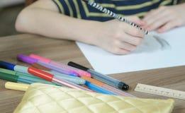特写镜头儿童` s手画与在白皮书的一支简单的铅笔和毛毡笔 免版税库存照片