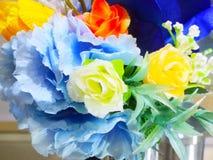 特写镜头几棵五颜六色的人造花花束背景 库存图片