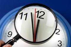 特写镜头击中午夜或中午的钟针通过放大镜 免版税图库摄影