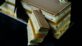 特写镜头切了多层焦糖蛋糕片断装饰用巧克力 股票录像