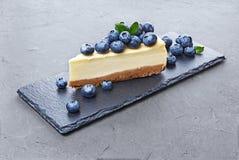 特写镜头切片可口自创乳酪蛋糕用在黑板岩板的新鲜的蓝莓 免版税库存图片