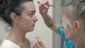特写镜头化妆师安置客户随后刺字的眼眉边界 股票录像