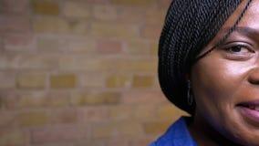 特写镜头半面孔射击成人非裔美国人女性微笑愉快地看的照相机户内在一栋舒适公寓 股票视频