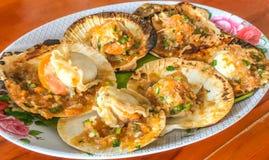 特写镜头可口烤扇贝用黄油和辣调味汁在壳在木桌背景,亚洲泰国海鲜 免版税库存图片
