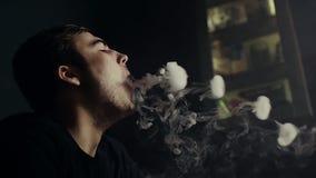 特写镜头可爱的人吹的烟圆环在慢动作的黑暗的水烟筒室 股票录像