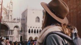 特写镜头后面视图被射击有戴着时髦的帽子和狂欢节面具在圣马尔谷教堂,威尼斯慢动作的长发的妇女 影视素材