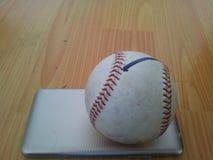 特写镜头和一个白色蟋蟀坚硬球的顶视图在巧妙的电话的在木地板上 免版税库存照片