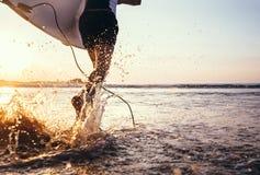 特写镜头图象水从冲浪者在海洋机智跑的` s腿飞溅 免版税库存照片