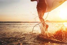 特写镜头图象水从冲浪者在海洋机智跑的` s腿飞溅 免版税图库摄影