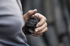 特写镜头在手边与煤炭小片断  库存图片