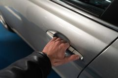 特写镜头在打开它-淡色汽车的车门的门闩的一只人的手 免版税图库摄影
