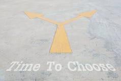 特写镜头在水泥街道地板上的表面老和淡黄的被绘的箭头标志与时刻选择词构造了背景 免版税库存图片