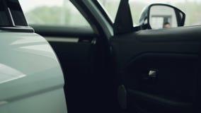 特写镜头在汽车经销权中在背景中射击了男性手开头车门与大窗口 卖汽车 股票录像