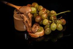 特写镜头在玻璃瓶子的巧克力花生酱用绿色葡萄 免版税库存图片