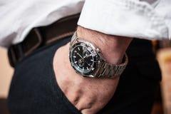 特写镜头在白色衬衫的人的手表 免版税库存图片