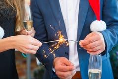 特写镜头在被弄脏的背景的人用香槟和闪烁发光物 在圣诞晚会概念的夫妇 免版税库存图片