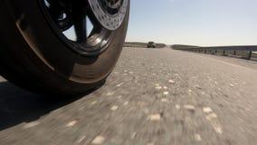 特写镜头在路非常快速地去的射击了摩托车轮子 股票录像