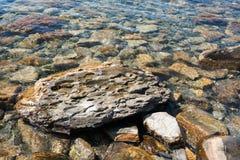 特写镜头在透明海水的一块大平的织地不很细石头 免版税库存图片