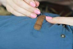 特写镜头女孩手对水兵厚实的织品的被缝合的皮革插入物是困难的刺穿针 免版税库存图片