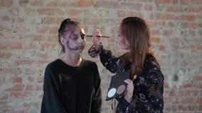 特写镜头妇女专业化妆师做蜡艺术戏院的塑料构成并且绘少女的面孔并且生成图象 股票视频