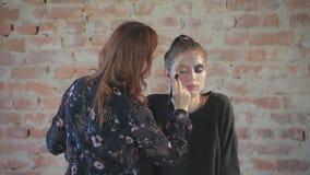特写镜头妇女专业化妆师做蜡艺术戏院的塑料构成并且绘少女的面孔并且生成图象 影视素材