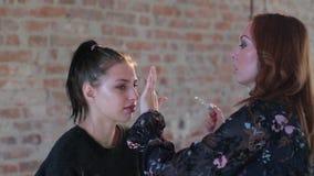 特写镜头妇女专业化妆师年轻逗人喜爱的俏丽的女孩的面孔为戏院的艺术性的构成做准备并且生成图象 股票录像