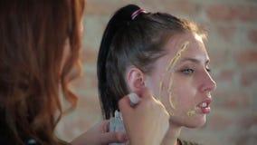 特写镜头妇女专业化妆师应用在年轻逗人喜爱的女孩的面孔的蜡塑料构成的戏院的并且生成图象 影视素材