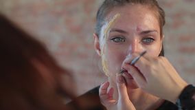 特写镜头妇女专业化妆师应用在年轻逗人喜爱的女孩的面孔的蜡塑料构成的戏院的并且生成图象 股票录像