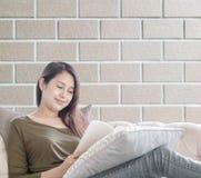 特写镜头妇女坐读的一本书沙发在业余时间下午在砖墙被构造的背景,放松a的时期 免版税图库摄影