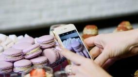 特写镜头妇女手拍紫色macarons的电话照片 股票录像