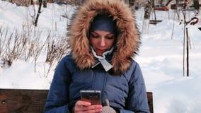 特写镜头妇女日间坐长凳和浏览手机在冬天公园在城市多雪的天气的 股票视频