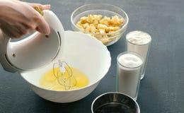 特写镜头妇女有搅拌器的` s手搅拌鸡蛋用在碗的糖 烹调苹果饼 免版税库存照片