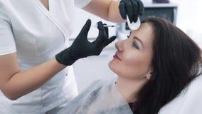 特写镜头妇女有注射器的面孔和美容师手做面部秀丽射入,慢动作 股票录像