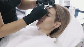 特写镜头妇女的有注射器的面孔和美容师的手做面部秀丽射入 股票视频