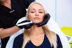 特写镜头妇女面孔和美容师手执行在患者的面孔的做法与与氢结合削皮用具 库存图片