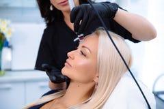 特写镜头妇女面孔和美容师手执行在患者的面孔的做法与与氢结合削皮用具 免版税库存照片