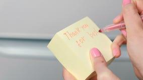 特写镜头妇女` s手在词在最佳的夜感谢您的黄色贴纸纸板料写 股票录像