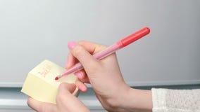 特写镜头妇女` s手在黄色贴纸纸板料词写在10:00 股票录像