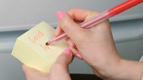 特写镜头妇女` s手在黄色贴纸纸板料词好运和绘画心脏写 影视素材