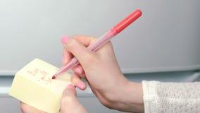 特写镜头妇女` s手在黄色贴纸纸板料词购买写:牛奶,面包,鸡 家庭笔记 影视素材