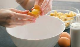特写镜头妇女` s手打破鸡蛋并且从卵黄质分离白色 免版税库存照片