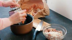 特写镜头妇女` s递在一台磨丝器的磨擦红萝卜在平底深锅 股票视频